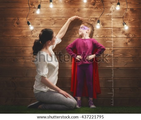 Mother measures the growth of her child daughter at a wooden wall. - stock photo