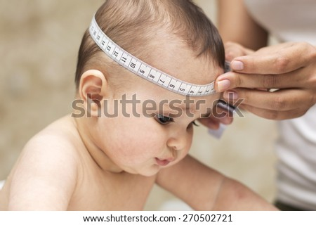 mother measures the size of the head of a beautiful baby child - stock photo