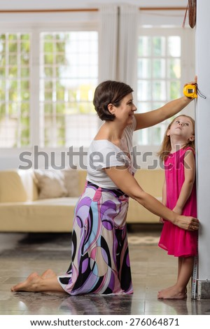 Mother measuring height of her daughter - stock photo