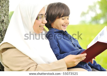 Mother Muslim and her son in the nature, reading together - stock photo