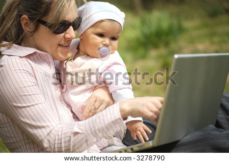 Mother of a 9 months old baby-girl is sitting on the ground in the garden and uses a laptop computer.