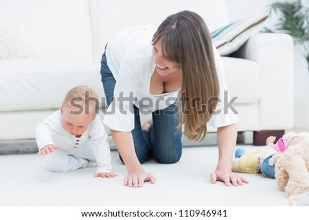 Mother on all fours next to a baby in living room - stock photo