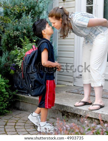 Mother on her front steps kissing her young elementary son good-bye as he heads out to school. - stock photo