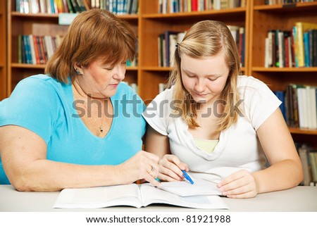 Mother, or teacher, helping a teenage girl with her homework.