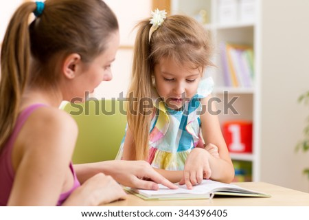 Mother or teacher helping child daughter to reading - stock photo