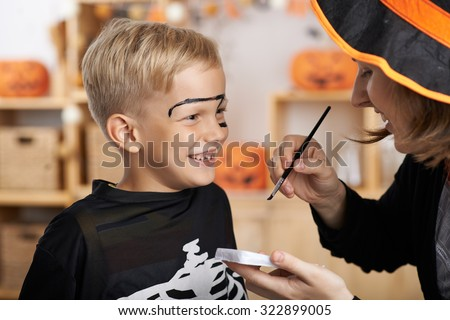 Mother painting face of her son for Halloween celebration - stock photo