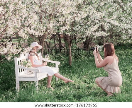 Mother photographing her daughter at spring garden - stock photo