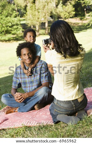 Mother photographing son and husband with digital camera in park. - stock photo