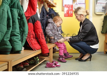 Mother picking up her child from a Kindergarten in wardrobe 2 - stock photo
