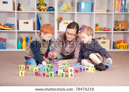 Mother playing blocks games with boys - stock photo