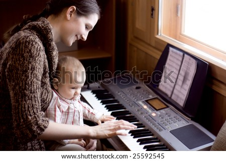 mother playing piano with her baby - stock photo