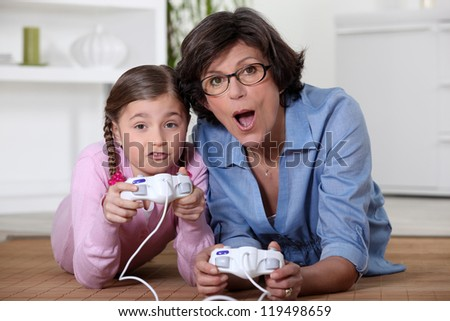 Mother playing vide-games with daughter - stock photo