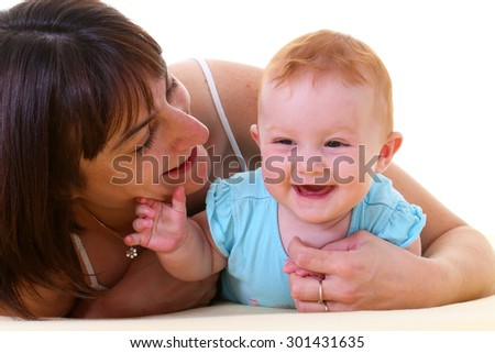 Mother playing with a baby in bed - stock photo