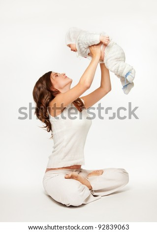 Mother playing with baby by lifting her and sitting in yoga pose - stock photo