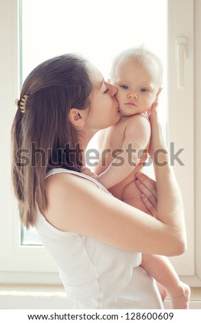 Mother playing with baby daughter - stock photo