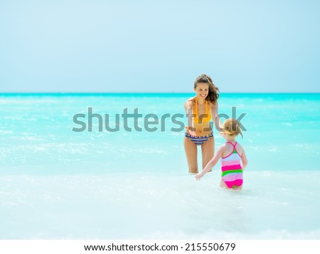 Mother playing with baby girl in sea - stock photo