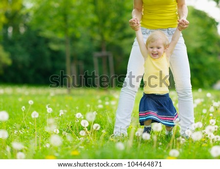 Mother playing with baby girl on dandelions field - stock photo