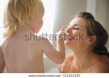 Mother playing with baby in bathtub - stock photo