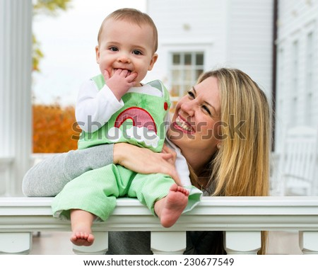 Mother playing with baby son at home on front porch - stock photo