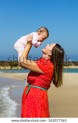 Mother playing with cute little daughter on the beach - stock photo