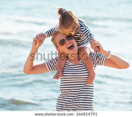 Mother playing with daughter on the beach - stock photo