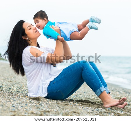 mother playing with her baby  on the beach on a sunny summer day - stock photo
