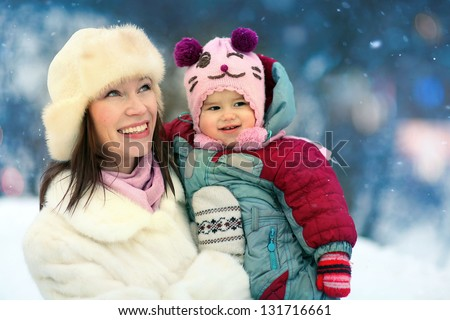 Mother playing with her baby outside in winter - stock photo