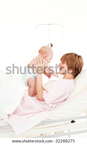 Mother playing with her baby son in hospital - stock photo
