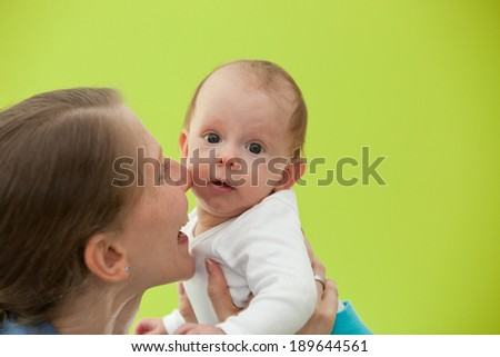 Mother playing with her beautiful little baby holding it up in the air as she laughs lovingly with the child looking towards the camera with big eyes, on a green background with copyspace
