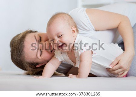 Mother playing with her cute baby  - stock photo