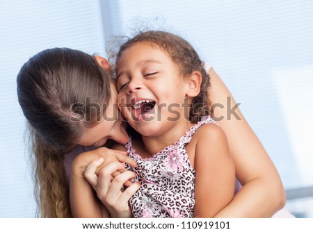 Mother playing with her happy daughter - stock photo
