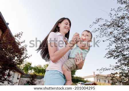 Mother playing with her little boy outdoors - stock photo