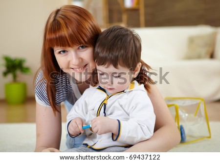 mother playing with her little son at home on the floor - stock photo