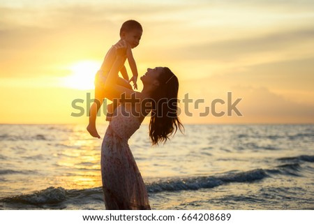 Mother playing with her son happily at the beach at sunset in holiday.