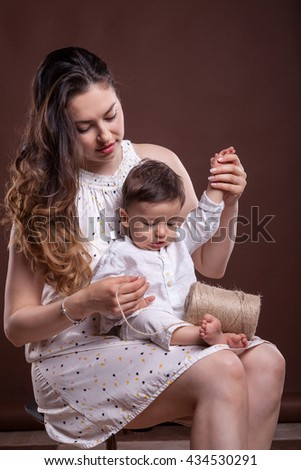 Mother playing with her son in studio on brown background