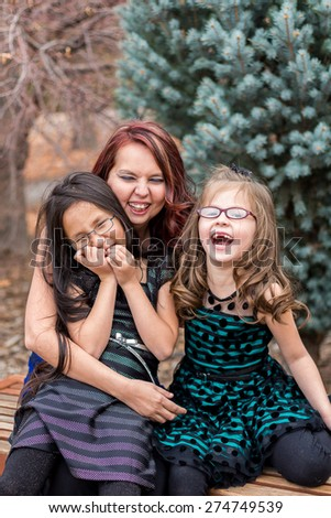 Mother playing with her young daughters outside at a park in Reno, Nevada, USA.  - stock photo