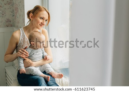 Mother playing with little daughter sitting on windowsill. Woman in jeans having fun with girl near window.