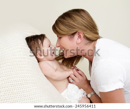 Mother Playing with Newborn Baby, Happy Laughing and Smiling - stock photo