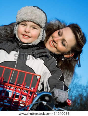Mother playing with son in winter - stock photo