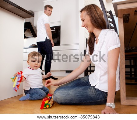 Mother playing with son on kitchen floor with father in background - stock photo