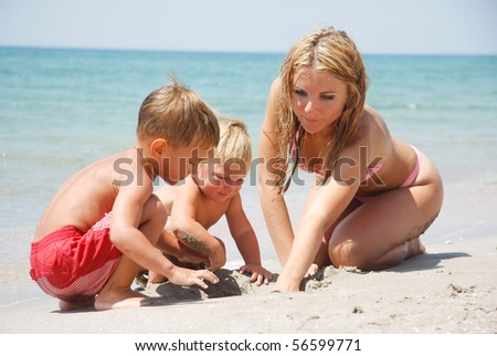 mother playing with two kids on beach - stock photo