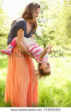 Mother Playing With Young Daughter In Summer Field - stock photo