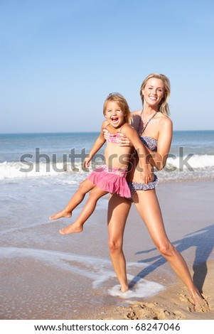 Mother playing with young girl on beach - stock photo