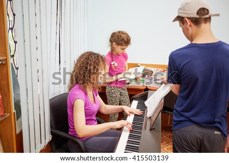 Mother plays piano, son turns over leaves of printed music and daughter reads book at room. - stock photo