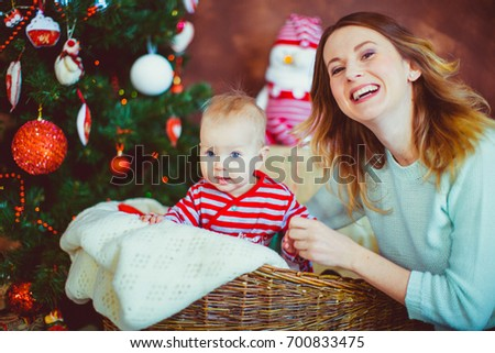 Mother plays with a boy who sits in the basket before a Christmas tree
