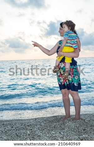 Mother pointing and showing something to her toddler boy on the beach at sunset - stock photo