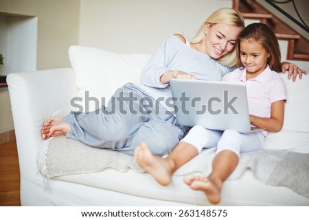 Mother pointing to computer and daughter looking at laptop and smiling - stock photo