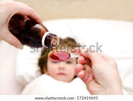 Mother pouring medication in a spoon in the foreground and sick little girl in the bed - stock photo