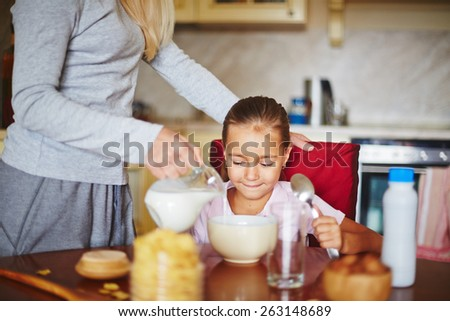 Mother pouring milk for daughter's breakfast - stock photo