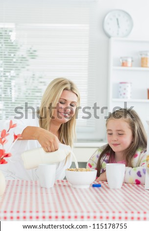 Mother pouring milk into cereal bowl for daughter at breakfast time in kitchen - stock photo
